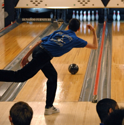 Bowling student from the high school releasing the bowling ball onto the lane. Bowling ball is aligned for a strike.